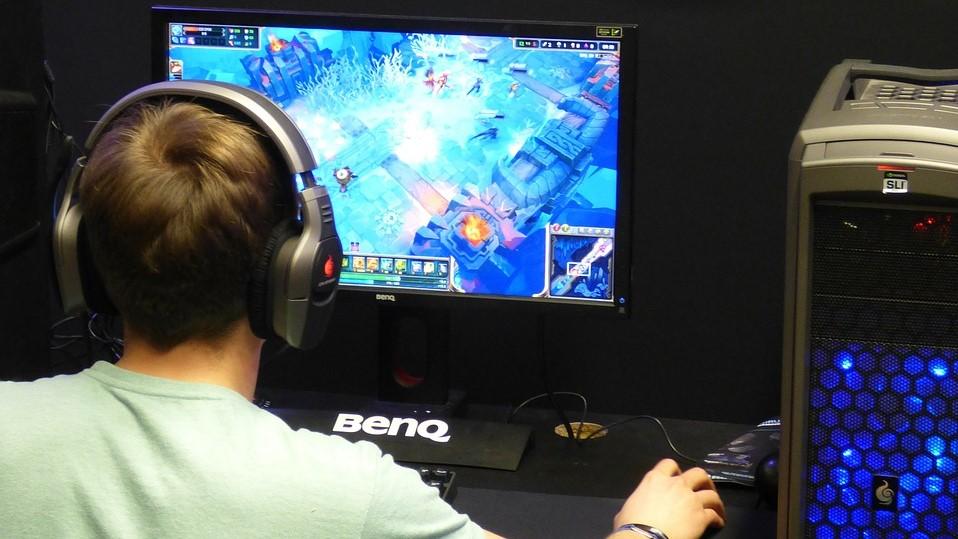 Einer Person mit Headset sitzt an einem Schreibtisch vor einem PC. Die Hand liegt auf der Maus, der Blick ist auf den Monitor gerichtet. Auf dem Bildschirm ist ein Videospiel zu sehen.