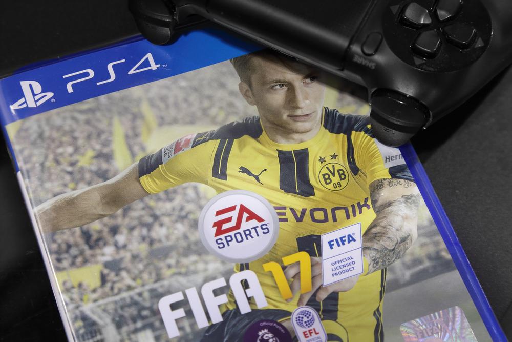 Das neue FIFA 17 mit Marco Reus auf dem Cover neben einem Playstation 4 Controller