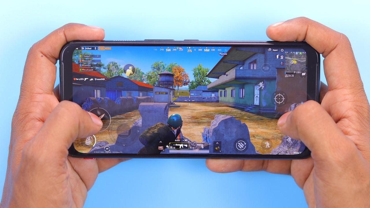 Wir sehen ein Smartphone, welches von zwei Händen gehalten wird. Auf dem Smartphone wird gerade die Mobile-Version von PUBG gespielt.