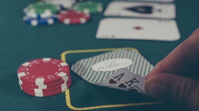 Zu sehen ist ein Blackjack-Tisch auf dem einige Karten und Spielchips liegen. Eine Hand deckt spitzen Fingern zwei Karten auf.