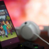 Ein Smartphone, welches auf einem Tisch auf einem kleinen Ständer steht. Neben dem Smartphone liegen kleiner Controller und Kopfhörer. Auf dem Smartphone ist die Minecraft Poket-Version zu sehen.