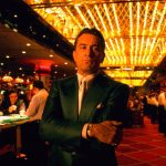 Ein Standbild aus dem Film Casino von 1995. Zu sehen ist Sam Rothstein (Ace), er inmitten eines Casinos steht. Um ihn herum wird Blackjack gespielt.